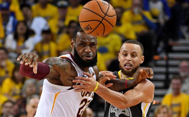 James (i) y Curry pugnan por el balón. /